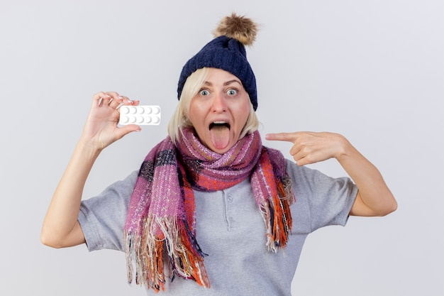 Aufgeregte junge blonde kranke slawische frau, die wintermütze und schal trägt