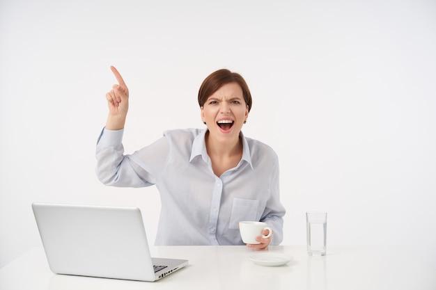 Aufgeregte junge braunäugige, ziemlich kurzhaarige dame in blauem hemd, die ihren zeigefinger hochhebt, während sie auf weiß mit weit geöffnetem mund sitzt