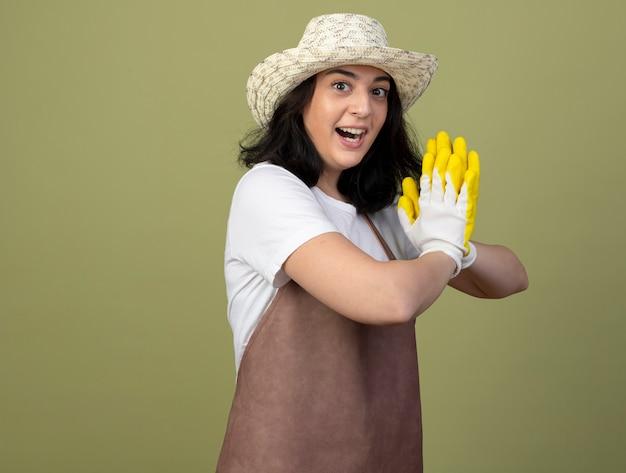Aufgeregte junge brünette gärtnerin in uniform, die gartenhut und handschuhe trägt, hält hände zusammen, die auf olivgrüner wand lokalisiert werden