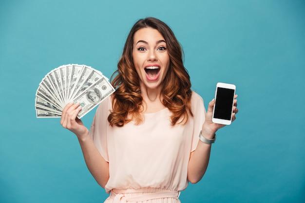 Aufgeregte junge dame, die anzeige des handys zeigt, das geld hält.