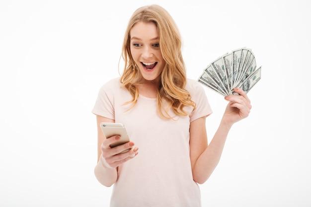 Aufgeregte junge dame, die geld unter verwendung des handys hält.