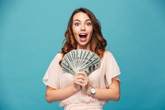 Aufgeregte junge dame, die geld zeigt.