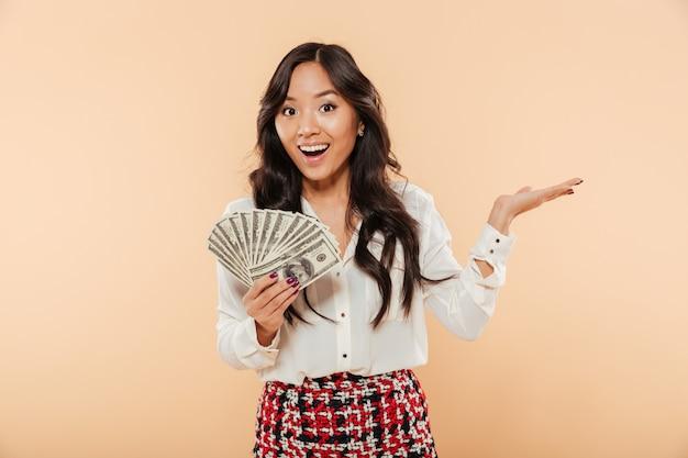 Aufgeregte junge dame mit dem langen dunklen haar, das fan von 100 dollarscheinen ausdrückt die freude, die viel geld über pfirsichhintergrund hat