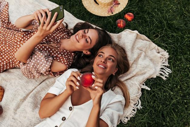 Aufgeregte junge damen in sommerlichen outfits picknicken auf grünem gras