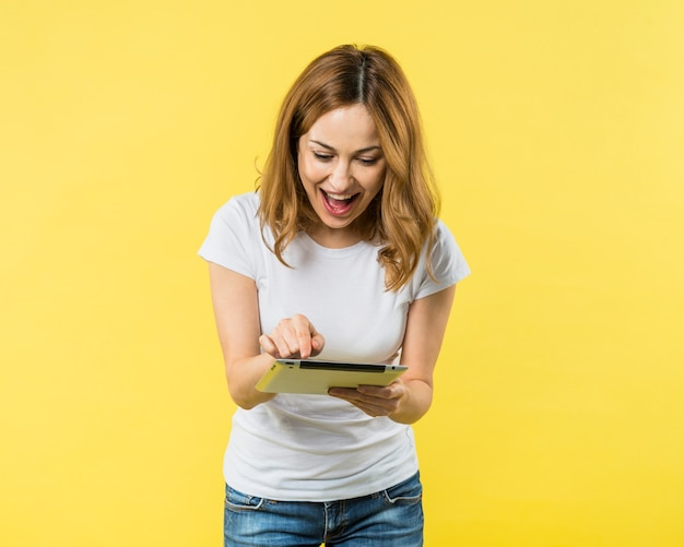 Aufgeregte junge frau, die den finger auf digitaler tablette gegen gelben hintergrund zeigt