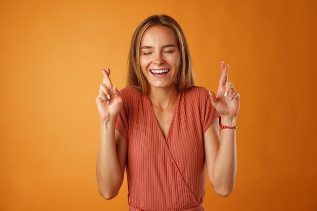 Aufgeregte junge frau, die gekreuzte finger für glück gegen orange hält