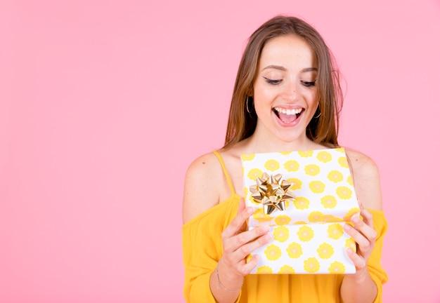 Aufgeregte junge frau, die gelbe tupfengeschenkbox mit goldenem bogen öffnet