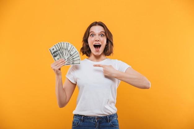 Aufgeregte junge frau, die geld hält und kamera zeigt.