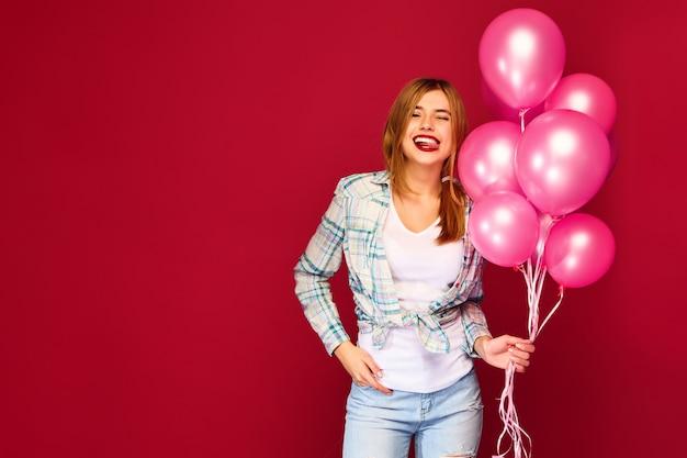 Aufgeregte junge frau, die mit rosa luftballons aufwirft