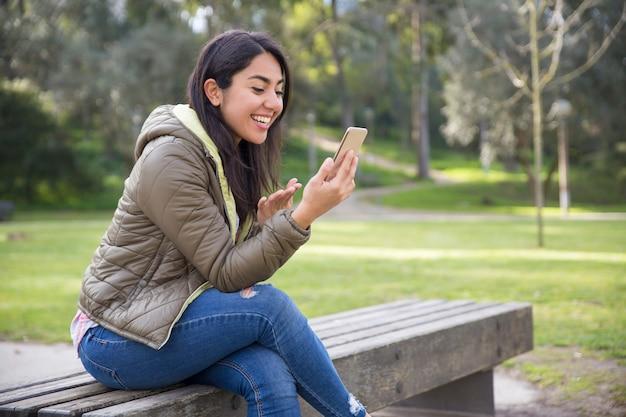 Aufgeregte junge frau, die online im park plaudert
