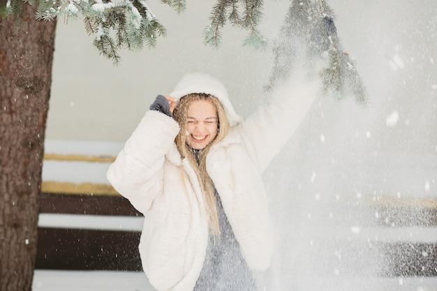Aufgeregte junge frau, die spaß mit schnee im park hat