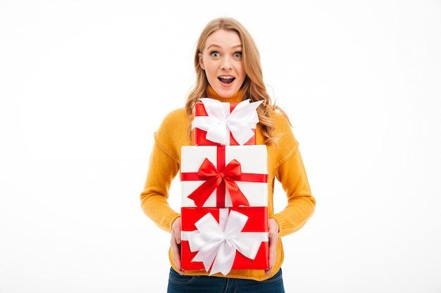 Aufgeregte junge frau, die überraschungsgeschenkboxen hält.