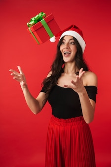 Aufgeregte junge frau, die weihnachtsmütze trägt, die lokal über rot steht und fliegende geschenkbox fängt