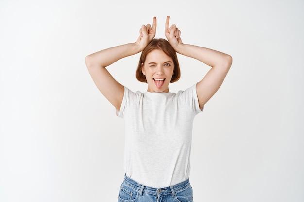 Aufgeregte junge frau, die zungen- und hörnerzeichen zeigt, glücklich zwinkert, in lässigem t-shirt und jeans auf weißer wand steht