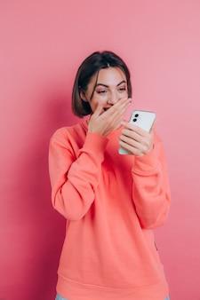 Aufgeregte junge frau erstaunt über unglaubliche verkaufsnachricht der mobilen app des einkaufs, die smartphone betrachtet, mädchengewinner, der handy hält, das vor freude schreit