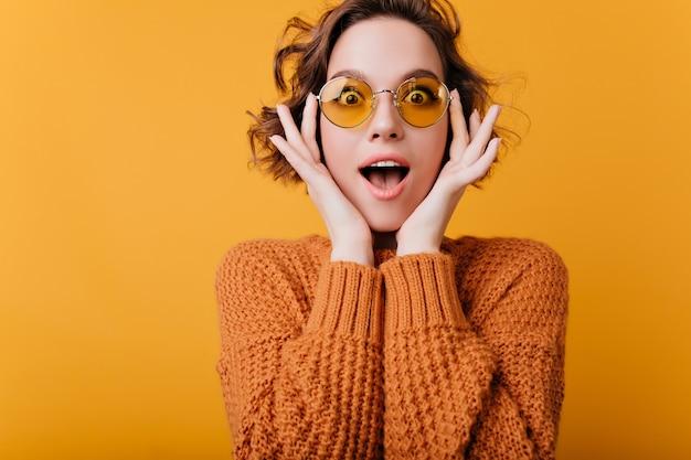 Aufgeregte junge frau in der runden gelben brille, die auf hellem raum aufwirft