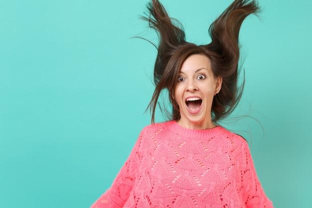 Aufgeregte junge frau in gestricktem rosa pullover mit flatternden haaren, die den mund weit offen hält und überrascht auf blauem hintergrund aussieht. menschen aufrichtige emotionen, lifestyle-konzept. kopieren sie platz.