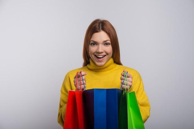 Aufgeregte junge frau mit einkaufstüten
