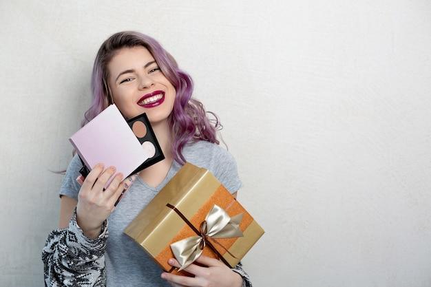 Aufgeregte junge frau mit lila haaren, die geschenkbox mit kosmetik hält. platz für text