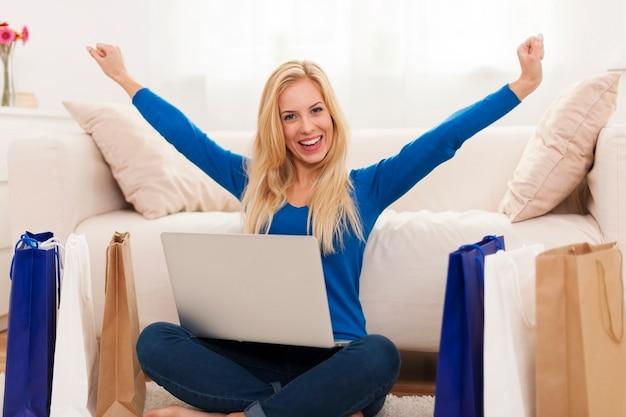 Aufgeregte junge frau mit online-shopping