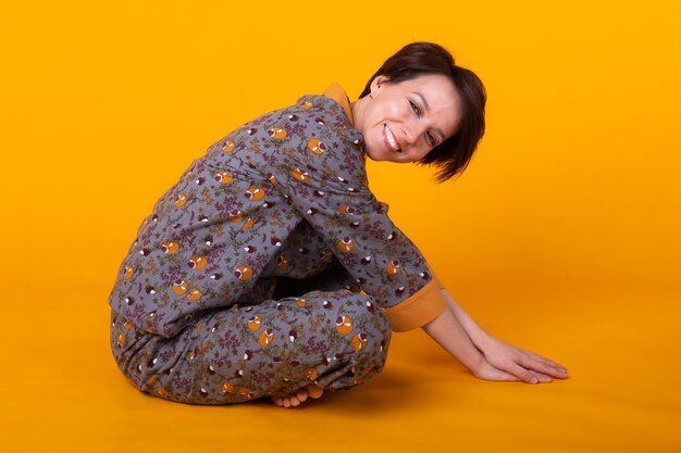 Aufgeregte junge frau mit schwarzen haaren im haus tragen pyjama, breit lächelnd spaß haben. isoliert am