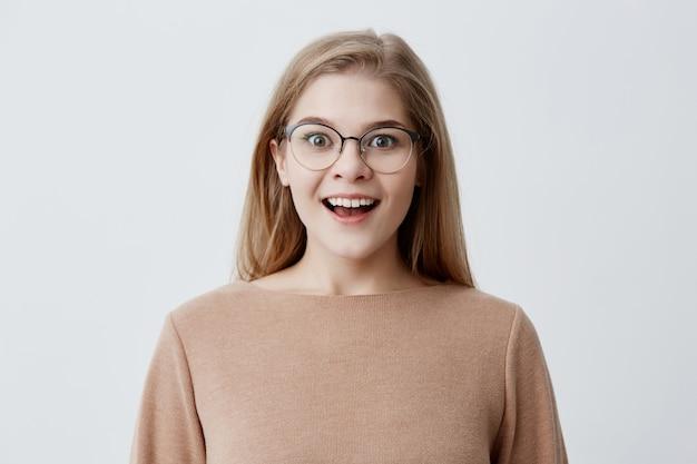 Aufgeregte junge frau von europäischem aussehen trägt braunen losen pullover, mit blonden haaren, in brillen, lächelt breit vor erstaunen und zeigt ihre perfekten weißen zähne. jugend und glück
