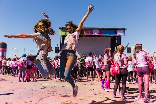 Aufgeregte junge frauen, die in einer luft feiert das holi festival springen