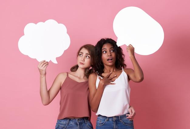 Aufgeregte junge frauen, die leere spracheblase halten