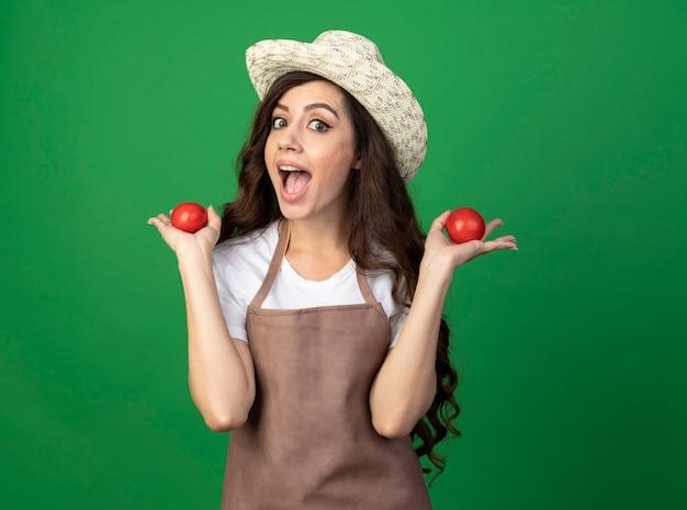 Aufgeregte junge gärtnerin in uniform mit gartenhut, die tomaten lokalisiert auf grüner wand hält