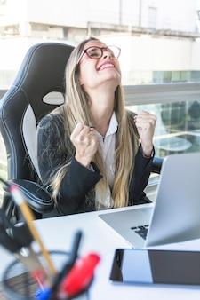 Aufgeregte junge geschäftsfrau, die am arbeitsplatz sitzt