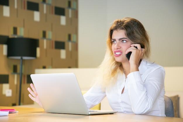 Aufgeregte junge geschäftsfrau, die am handy im gemeinsamen arbeitsraum spricht und am tisch mit laptop sitzt