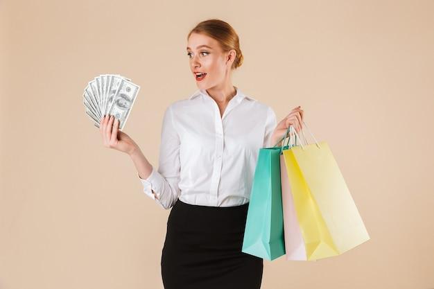 Aufgeregte junge geschäftsfrau, die einkaufstaschen und geld hält