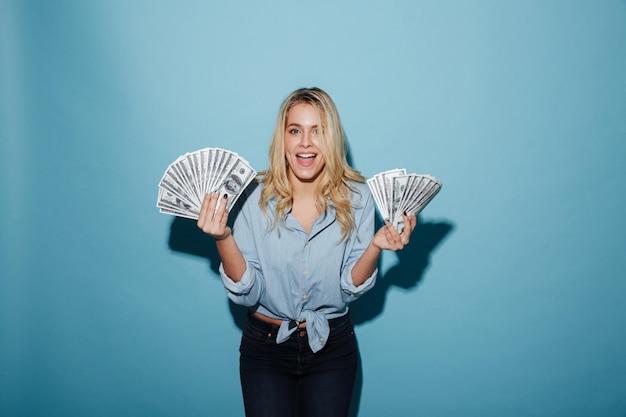 Aufgeregte junge hübsche blondine, die geld in den händen halten.