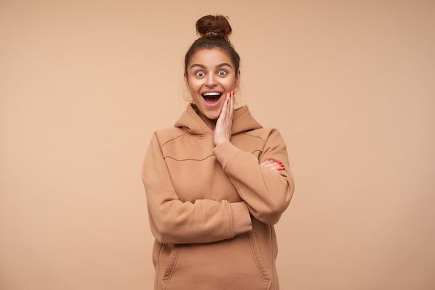 Aufgeregte junge hübsche brünette frau gekleidet in nacktem sweatshirt, die handfläche auf ihrer wange hält, während sie mit großen augen und geöffnetem mund, der über beige wand isoliert ist, erstaunt nach vorne schaut
