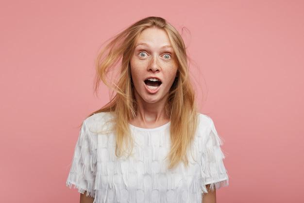 Aufgeregte junge hübsche rothaarige frau mit wildem haar, das aufgeregt mit geöffneten augen in die kamera schaut und überraschend augenbrauen hochzieht, während sie über rosa hintergrund posiert