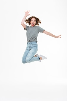 Aufgeregte junge kaukasische dame, die springt