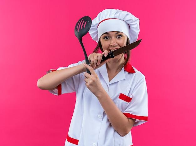 Aufgeregte junge köchin, die kochuniform trägt und messer mit spachtel auf rosa hintergrund hält