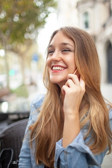 Aufgeregte junge lachende frau bei am telefon draußen sprechen