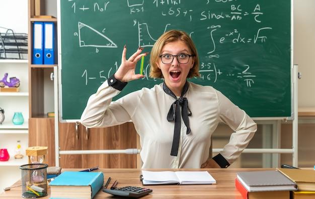 Aufgeregte junge lehrerin sitzt am tisch mit schulwerkzeugen, die einen bleistift halten und die hand ins klassenzimmer legen