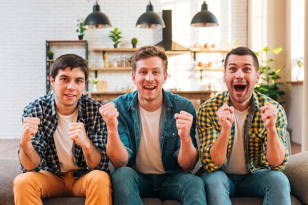 Aufgeregte junge männer, die auf dem zujubelnden sofa beim aufpassen des matches im fernsehen sitzen