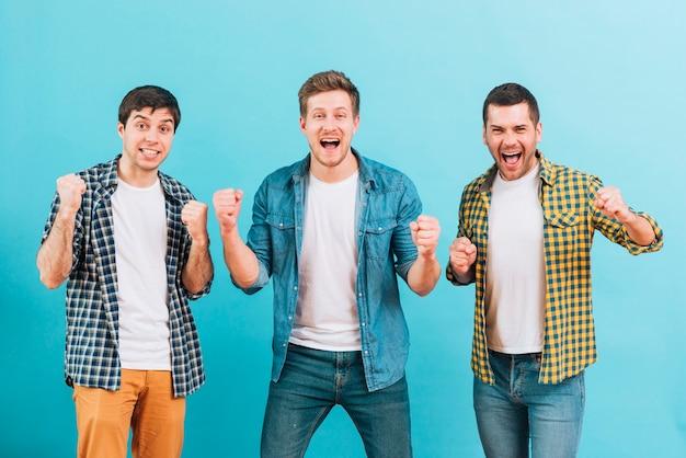 Aufgeregte junge männliche freunde, die ihre faust gegen blauen hintergrund zusammenpressen