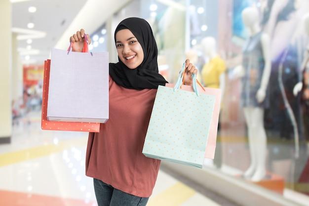 Aufgeregte junge muslimische frau beim einkaufen, die papiertüte in ihrer hand am einkaufszentrum hält