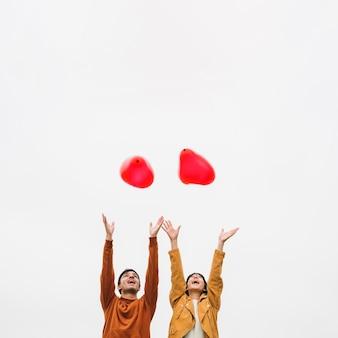 Aufgeregte junge paare, die ballone gehen lassen