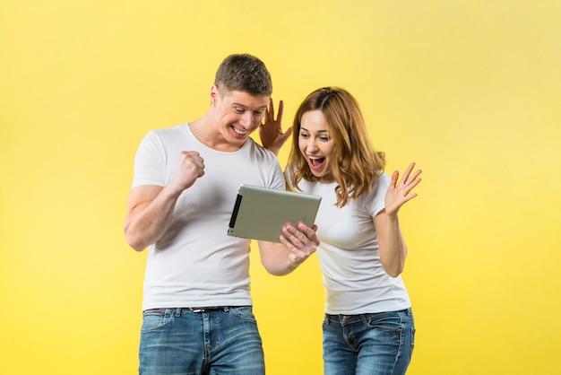 Aufgeregte junge paare, die digitale tablette gegen gelben hintergrund betrachten