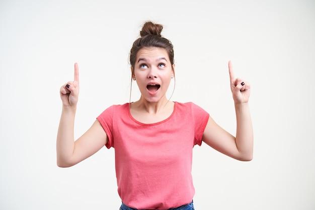Aufgeregte junge schöne braunhaarige frau, die ihren mund offen hält, während sie aufgeregt mit zeigefingern nach oben zeigt, isoliert über weißem hintergrund