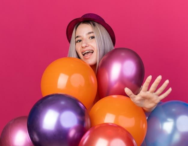 Aufgeregte junge schöne frau mit partyhut mit zahnspangen, die hinter ballons steht und die hand vorne isoliert auf rosa wand hält