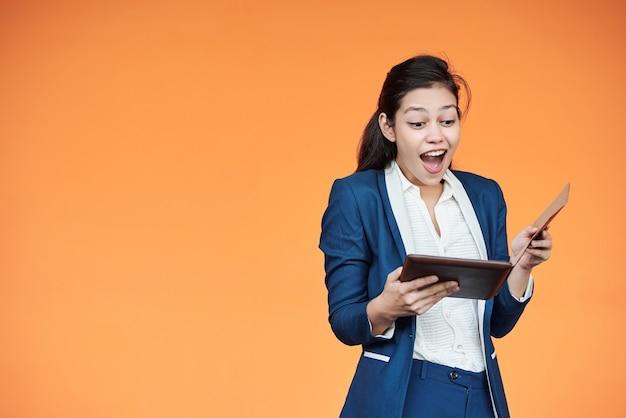 Aufgeregte junge unternehmerin, die e-mails auf tablet-computer mit guten nachrichten überprüft