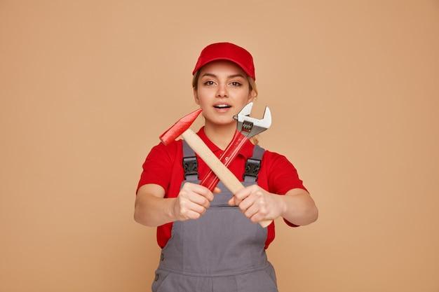 Aufgeregte junge weibliche bauarbeiterin, die mütze und uniform trägt, die schraubenschlüssel und hammer in richtung kamera ausstrecken und keine geste tun