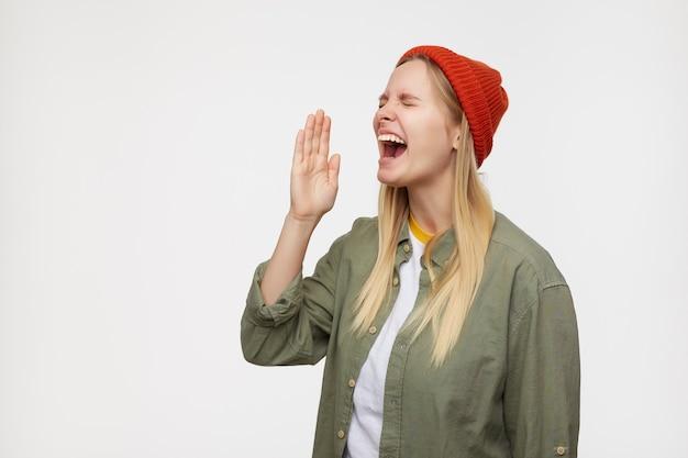 Aufgeregte junge ziemlich langhaarige blonde dame, die ihre augen geschlossen hält, während sie schreit und die hand vor den mund hebt, freizeitkleidung trägt und auf blau posiert