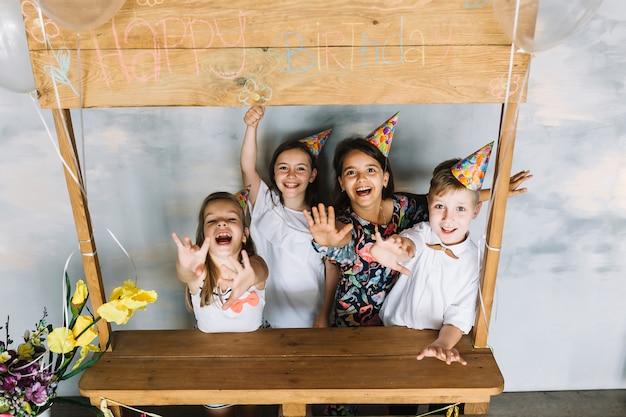 Aufgeregte kinder, die heraus arme auf geburtstagsfeier ausdehnen